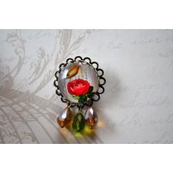 Suure punase roosi, kollase linnu ja rippuvate klaashelmestega pross